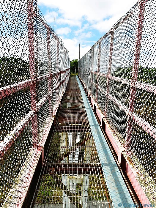 Caged walkway across pipelines near Miford Haven forming part of The Wales Coast path in Pembrokeshire, photographed by Charles Hawes