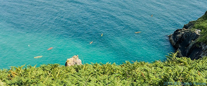 canoeists in Fishguard Bay photographed from The wales Coast path by Charles Hawes