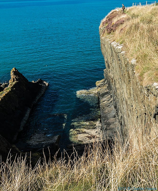 Sheer cliff face between Cwm-yr-Eglwys and Newport on The wales Coast path in Pembrokeshire, photographed by Charles Hawes