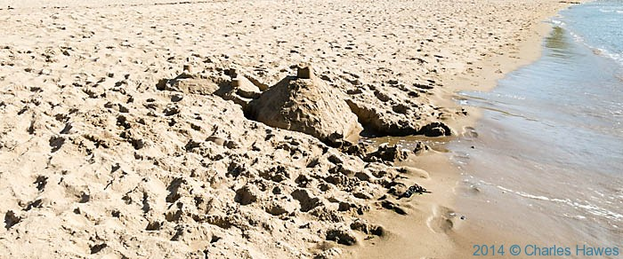 Sandcastle on the beach at Whistling Sands, photographed from The Wales Coast path by Charles Hawes