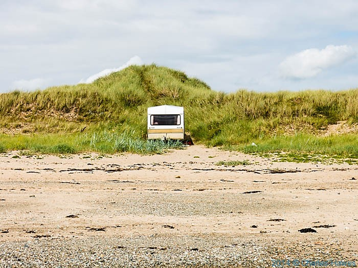 Caravan on the beach at Rhosneigr, Anglesey, photographed from the Wales Coast Path by Charles Hawes