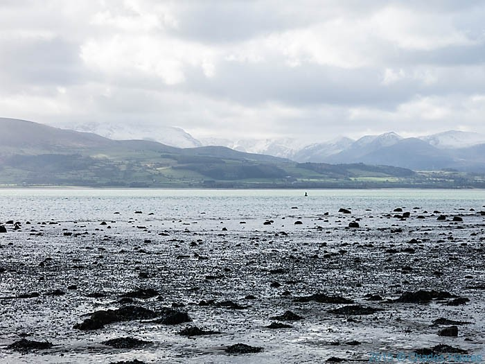 View to Snowdonia from across Menai Strait, Anglesey, photographed from The Wales Coast Path by Charles Hawes