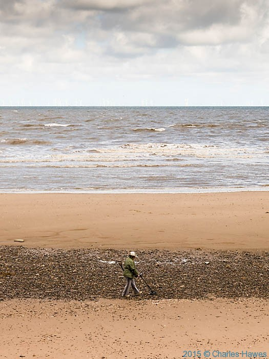 Metal detectorist on Rhyl beach, photographed from The Wales Coast Path by Charles Hawes
