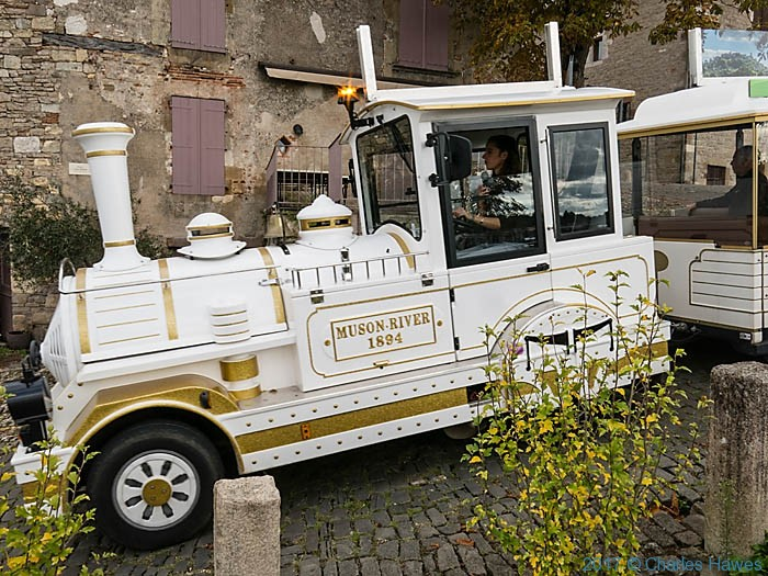 Tourist bus in Cordes sur Cilel, France, photographed by Charles Hawes