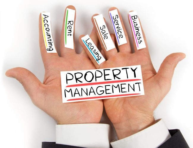Photo of hands holding paper cards with PROPERTY MANAGEMENT concept words