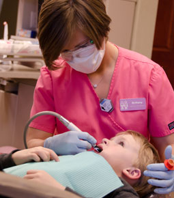 Photo of female hygienist cleaning boy's teeth