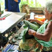 Local woman cutting palm leaf hats