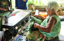 Local woman cutting palm leaf hats