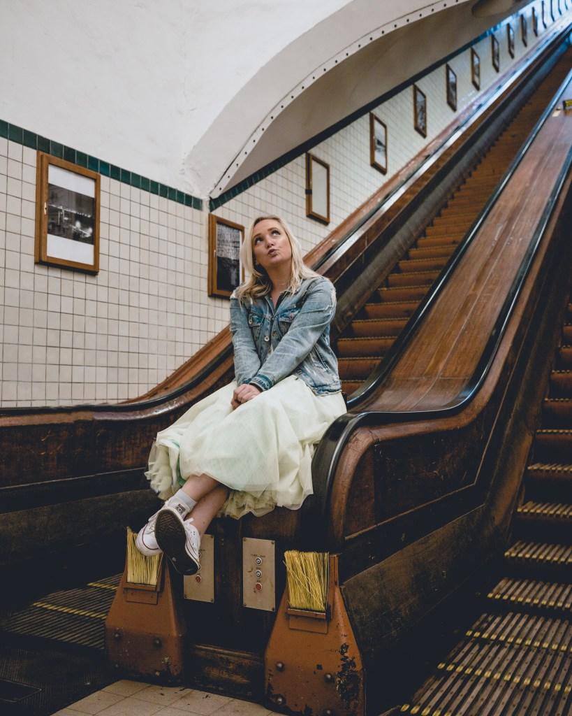 girl sitting on underground vintage escalator