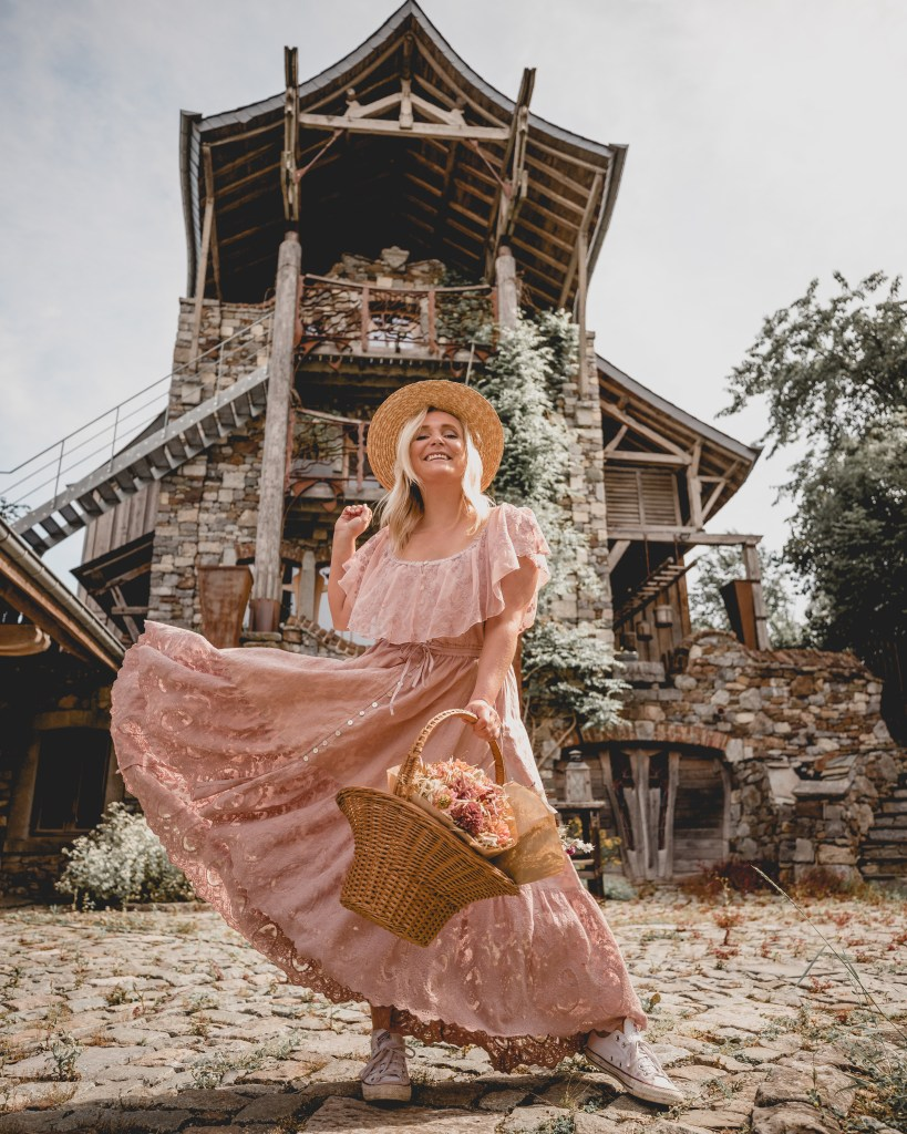 girl standing in front of fairytale house