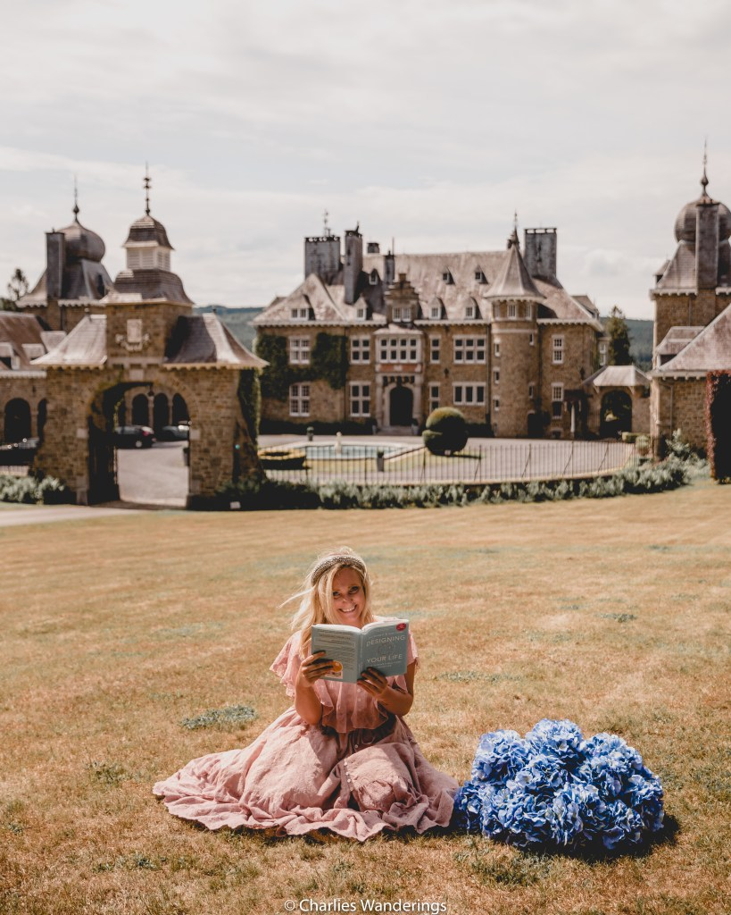 Girl reading a book in front of castle