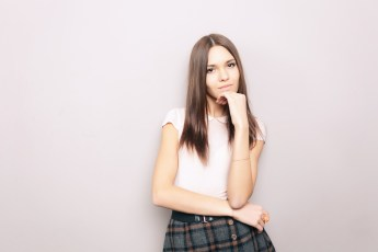Young thoughtful beautiful brunette lady posing indoors against wall