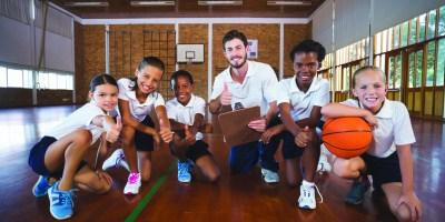 Kids enjoying their school gymnasium by playing a game of basketball.