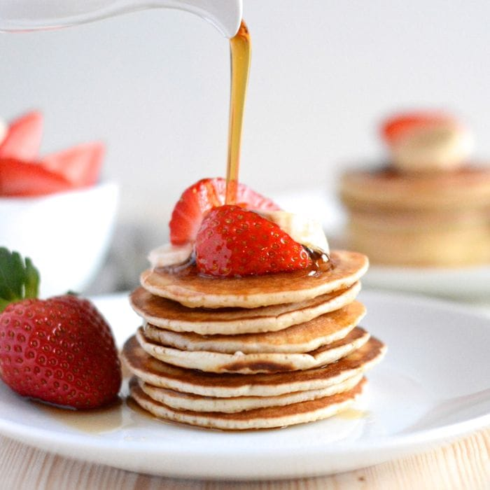 Maple syrup being poured onto a stack of American pancakes topped with fresh strawberries.