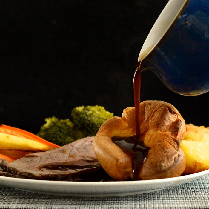Gravy being poured onto a plate of roast beef with homemade Yorksire puddings.