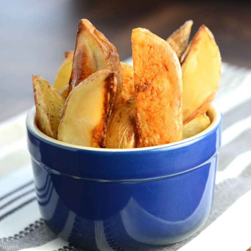 Homemade potato wedges in a blue pot.