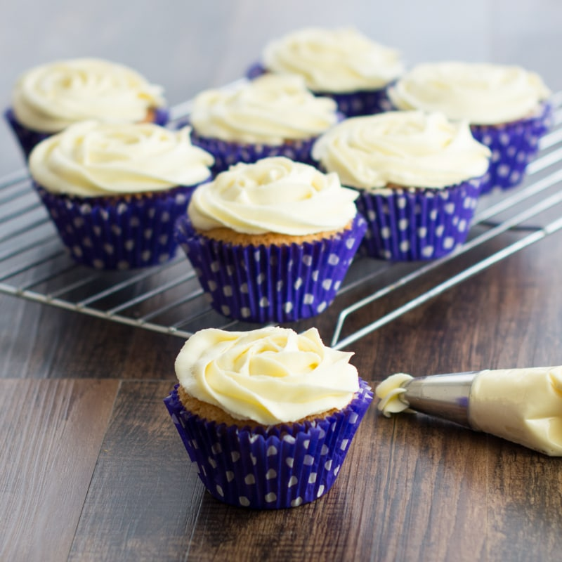 A selection of vanilla cupcakes topped with vanilla buttercream and a piping bag full of vanilla buttercream.