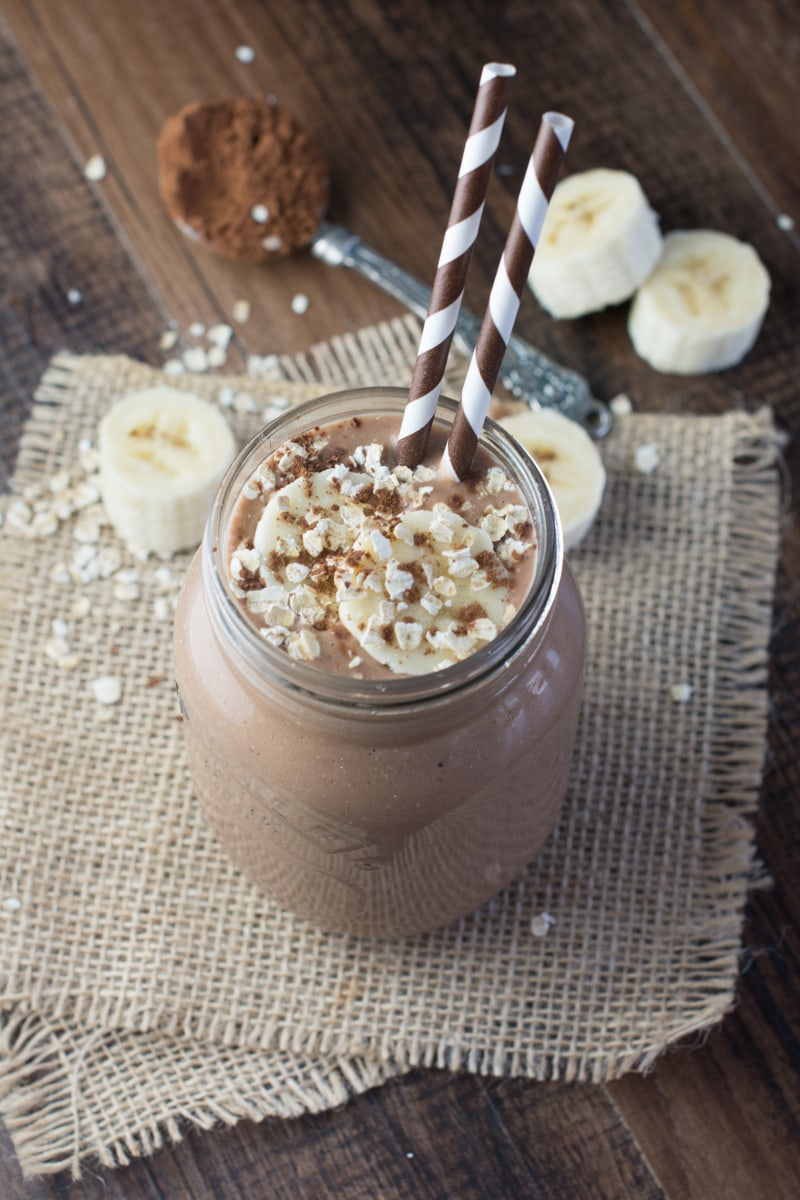 Coconut, Banana & Chocolate Breakfast Smoothie in a mason jar with two brown striped straws. The smoothie is topped with slices of banana and oats.