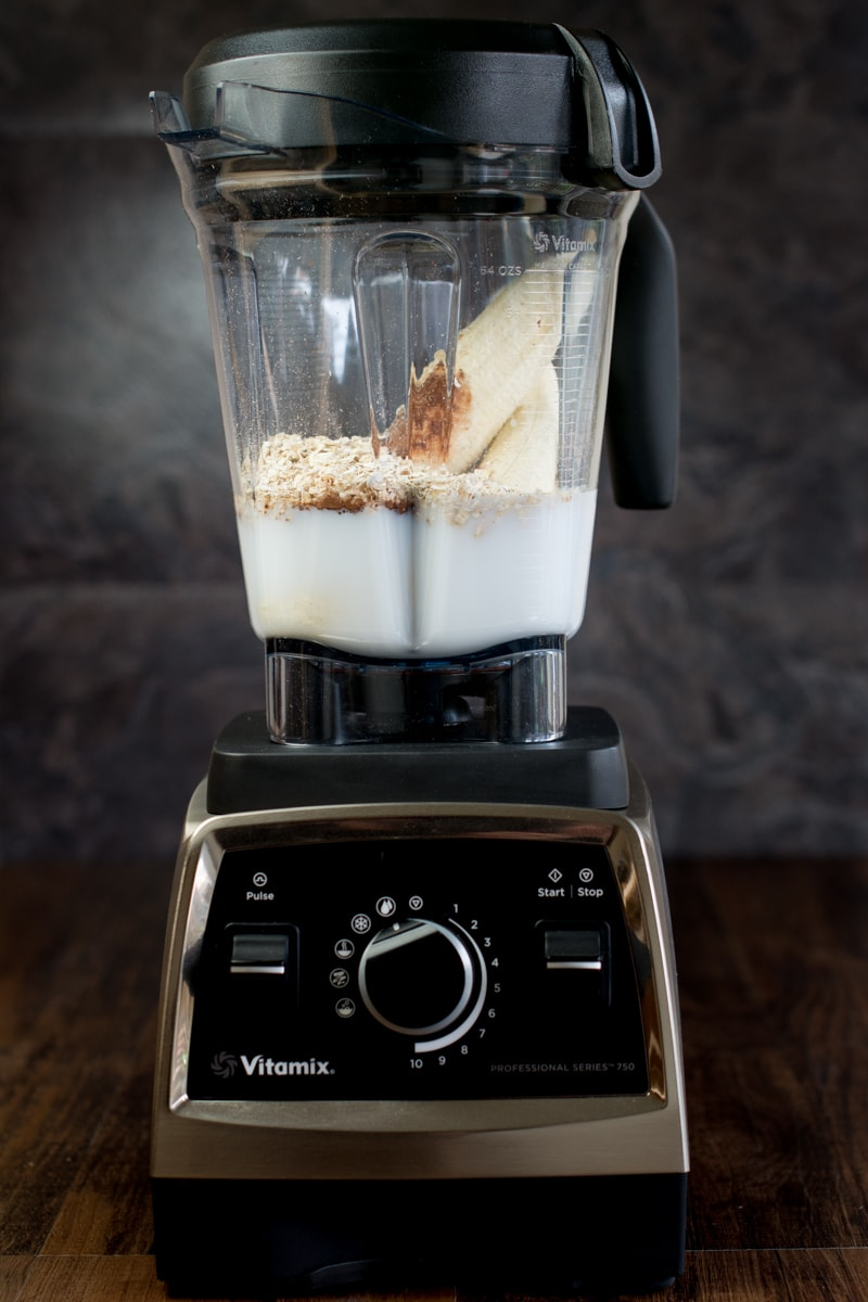 My Vitamix 750 filled with banana, cocoa powder, oats, vanilla extract and coconut milk, ready to make a delicious coconut, banana and chocolate smoothie.