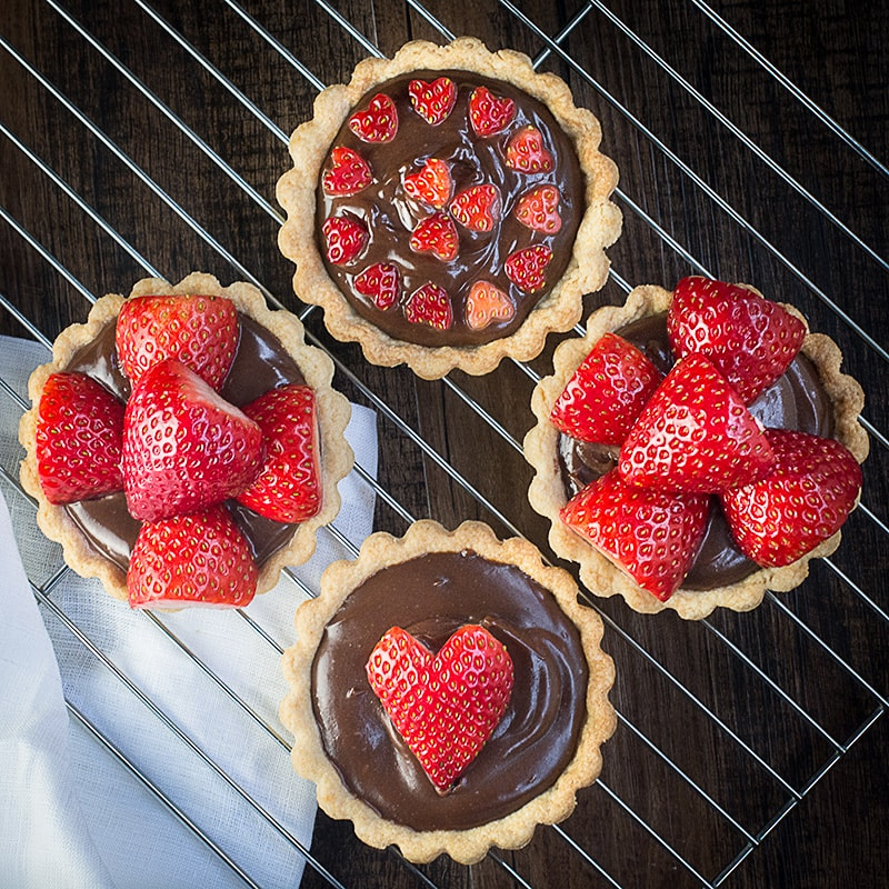 Treat someone you love with these strawberry and champagne truffle tarts - a sweet shortcrust pastry tart filled with rich milk chocolate and champagne ganache and topped with champagne soaked strawberries.