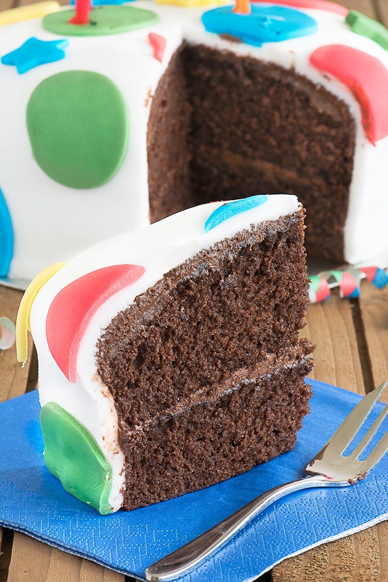 A slice of chocolate birthday cake filled with chocolate buttercream and covered with fondant icing. The rest of the cake is in the background with a gap showing where the slice had come from.
