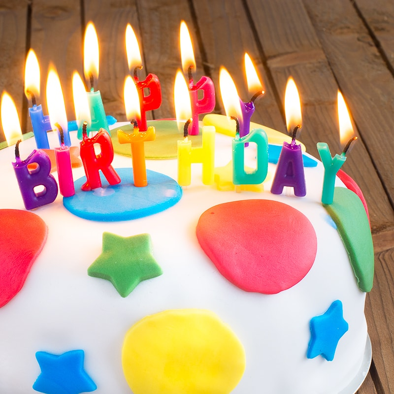 """A round birthday cake covered in white fondant icing decorated with multi-coloured stars and circles. The cake is topped with burning candles spelling """"HAPPY BIRTHDAY"""""""