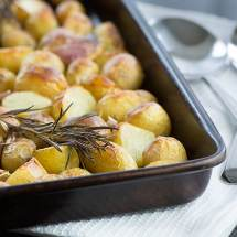 Roasted new potatoes in a baking tray topped with a sprig of rosemary.