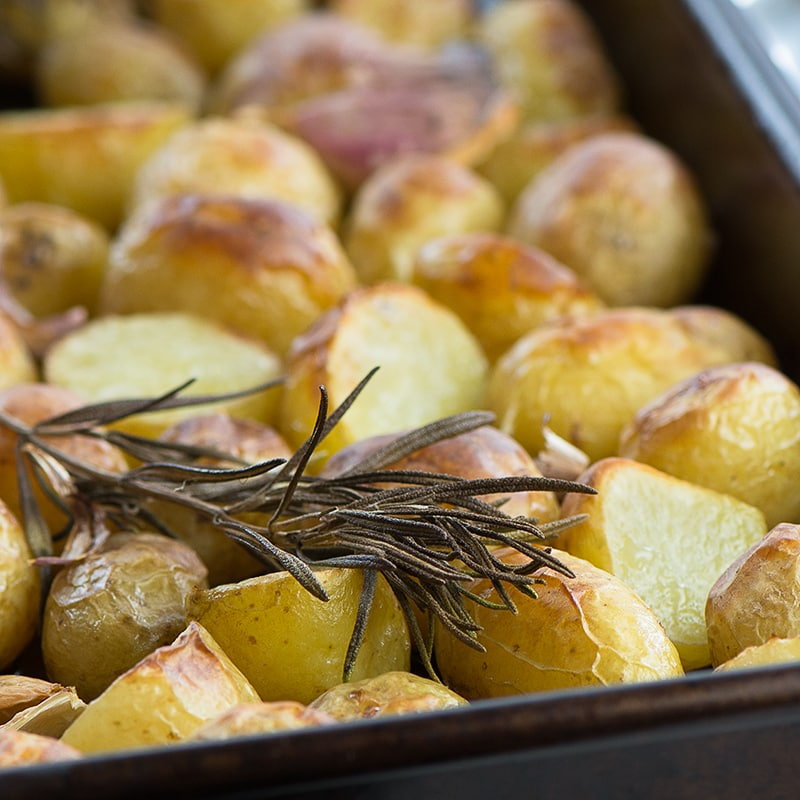 Roasted new potatoes in a baking tray.
