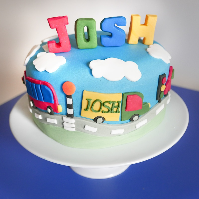 A child's transport birthday cake with cars, lorries, tractors, buses and even a cement mixer!