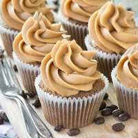 Coffee cupcakes topped with coffee buttercream on a wooden board with cake forks at the side.