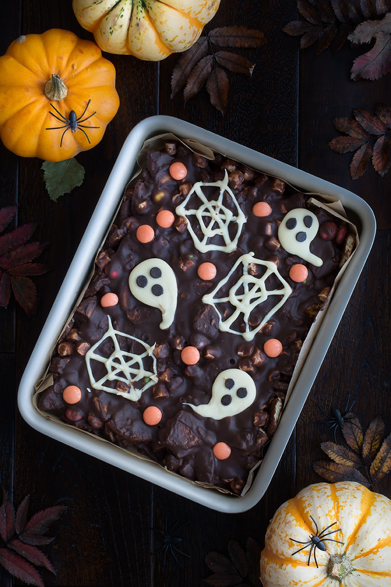 Spooky Rocky Road - a delicious and easy to make Halloween treat packed with crunchy biscuits, Smarties, marshmallows and lots of chocolate. There's an option to make it taste like Chocolate Orange too!