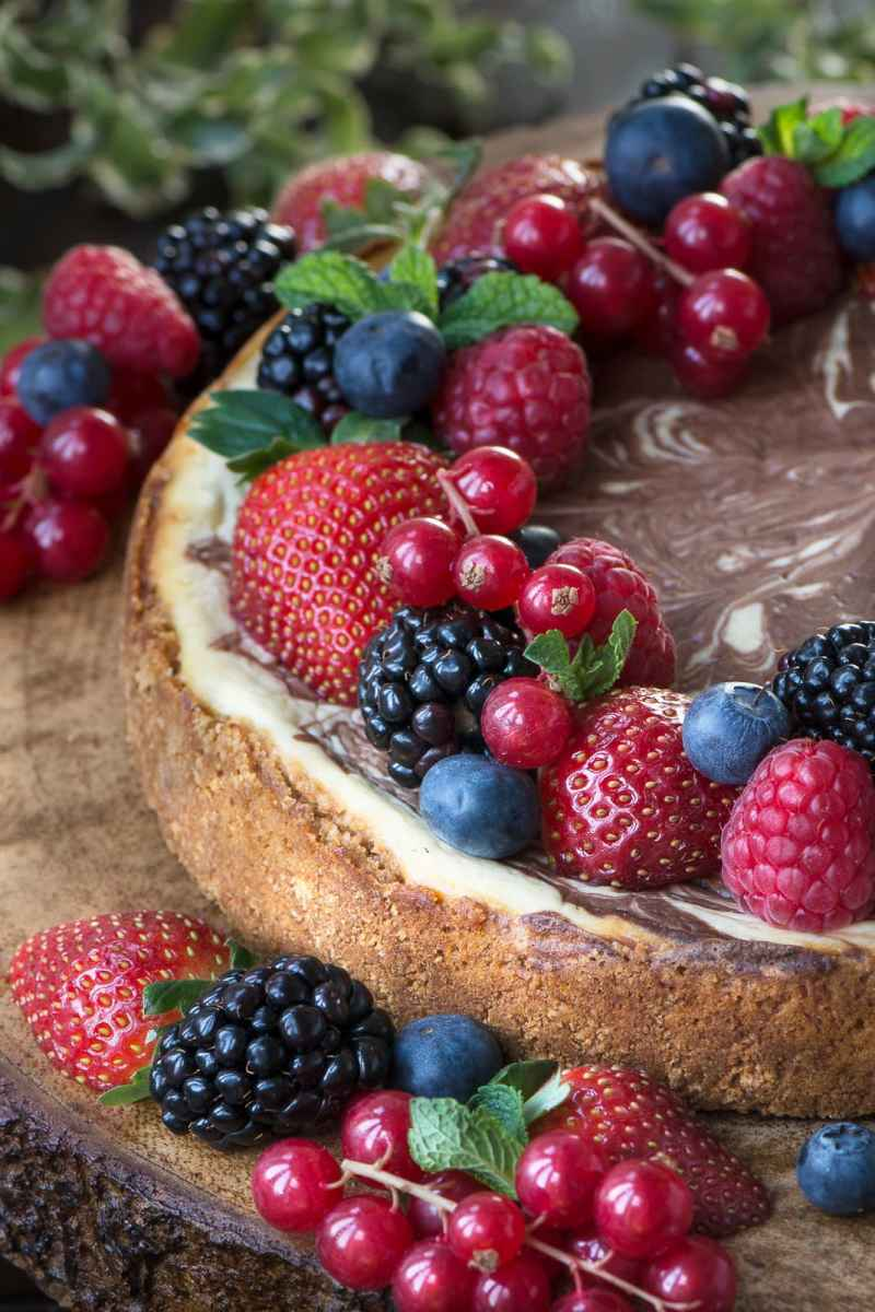 Baked chocolate marble cheesecake topped with fresh strawberries, blackberries, blueberries, raspberries, redcurrant and mint leaves.