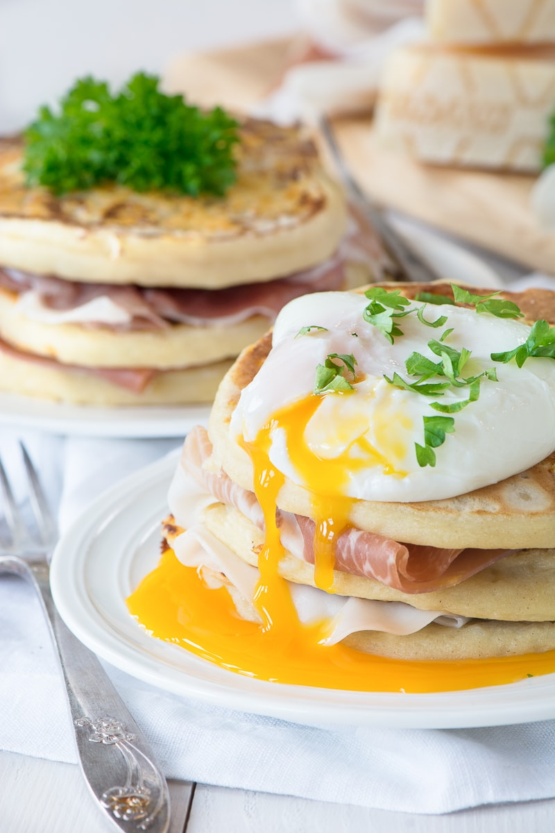 Two stacks of Grana Padano pancakes, one toped with a packed egg. Layered with Prosciutto di San Daniele.