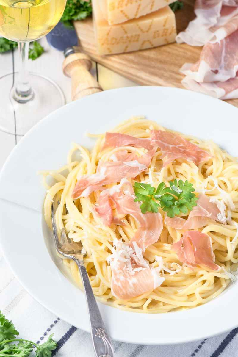 A bowl of creamy Spaghetti Carbonara made with Prosciutto di San Daniele and Grana Padano cheese. Served with a glass of white wine.