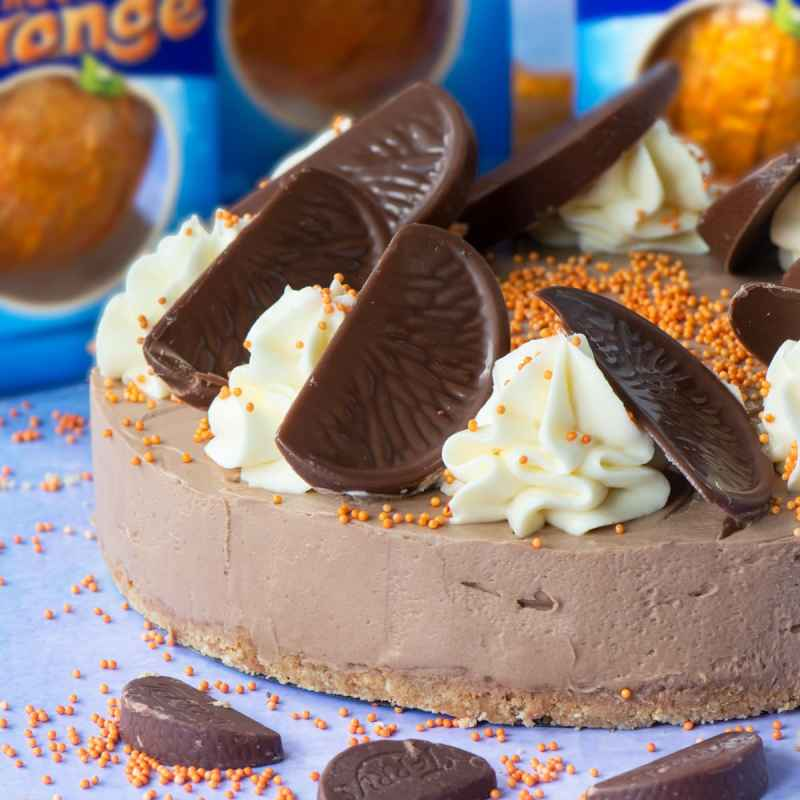 Chocolate Orange Cheesecake - A delicious and easy to make no-bake dessert. A smooth chocolate orange flavoured cheesecake topped with swirls of white chocolate orange cheesecake and slices of Chocolate Orange. A dessert lover's dream.