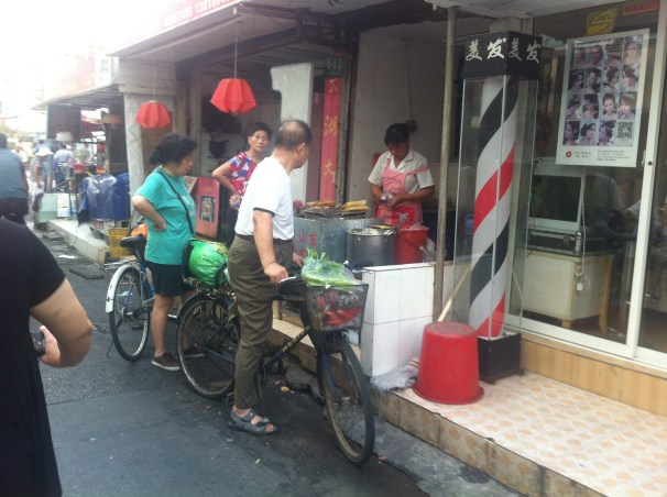 The locals buy some food from a street vendor on Anxi Road. These types of stands are common on the small streets of Shanghai.
