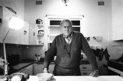 Patrick White, presumably in his kitchen. Picture reproduced by The Age in 2006; photographer unacknowledged in this version online.