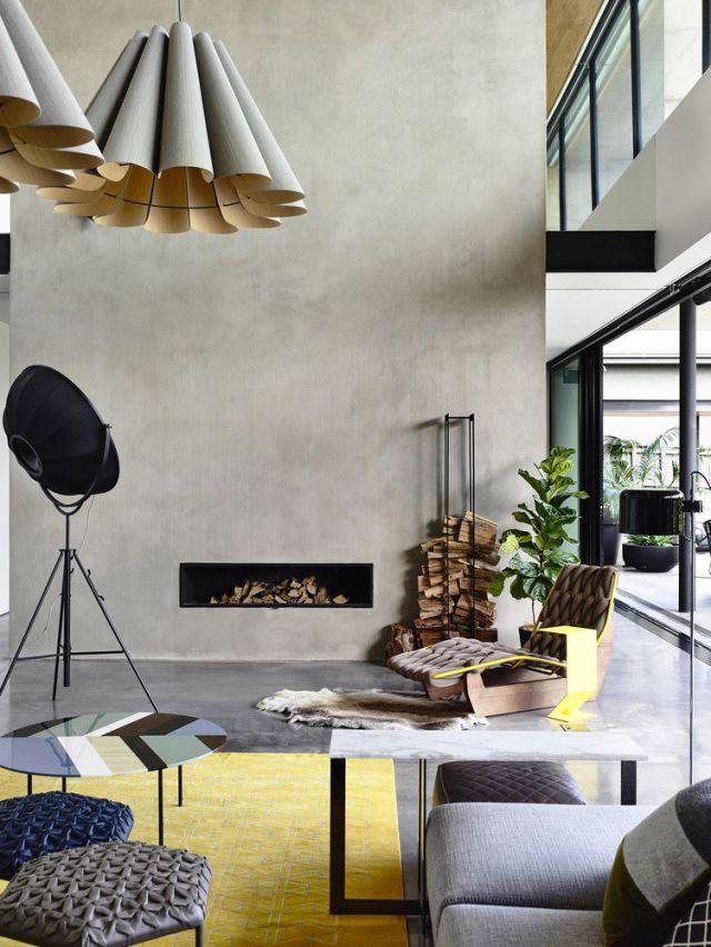 ダブルハイトのリビングエリアには、磨かれたコンクリートの床、ミニマリストの暖炉、特大のペンダントランプがあります