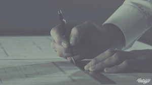 man's hands holding ruler and pencil, with architectural drawings