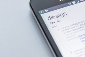iphone with screen showing definition of design