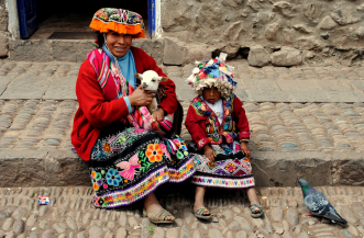 Indigenous Peruvian woman and boy, dressed in traditional colorful clothing