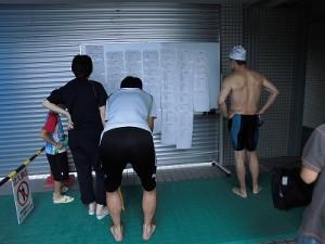 水泳大会の応援に行って来ました。 競技結果に見入る人達/どこまでもアマチュア