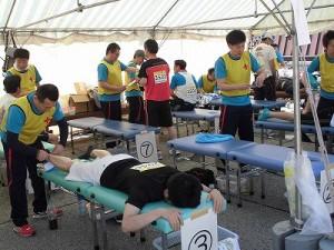 柔道整復師ボランティアに身体の状態を調整してもらっているマラソンランナー