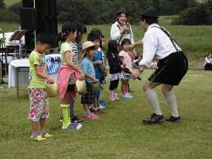 六呂師高原アルプス音楽祭2015 アルプス音楽団 チビッ子たちにクーグロッケンを手渡す竹田 年志氏/どこまでもアマチュア