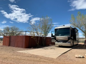 An RV on a concrete pad, with a fenced in area containing a patio. Trees on either side.