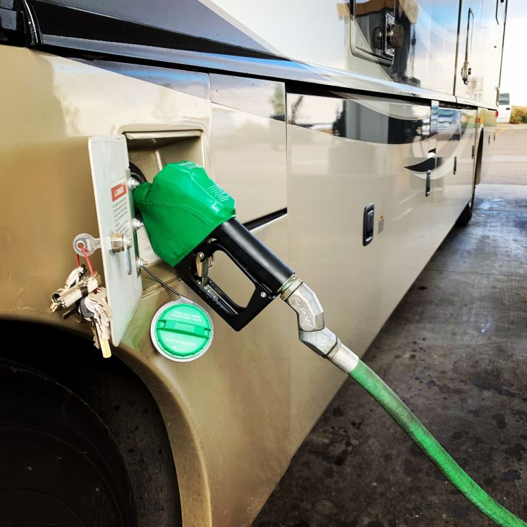 Fueling up with diesel at the gas station, showing a green pump handle in the RV tank.
