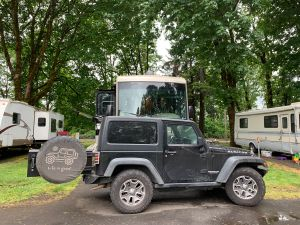 Our Jeep Wrangler in front of our RV, surrounded by trees.