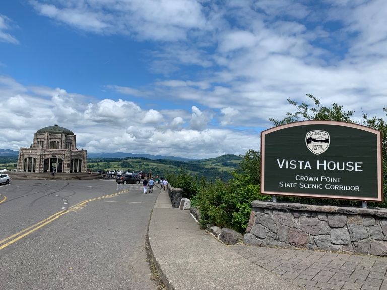 Vista House in the distance, with the sign in the foreground.