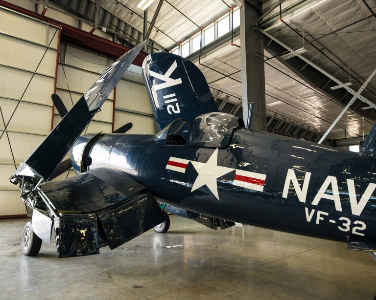 A Vought F4U Corsair plane, looking from the rear left side.