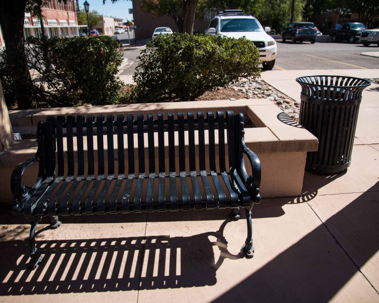 A bench and trash can with cool shadows.